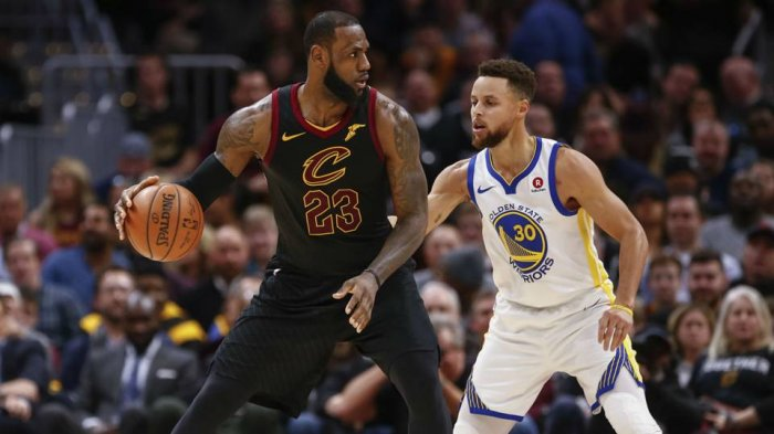Bintang Cleveland Cavaliers LeBron James (kiri) berhadapan dengan guard Golden State Warriors Stephen Curry dalam final pertama NBA 2018 di Oracle Arena, Jumat (2/6/2018) pagi WIB.