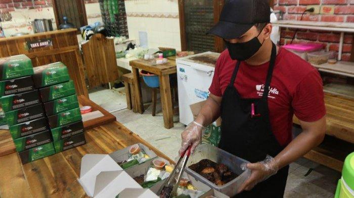 DISIPLIN J3K - Karyawan Rumah Makan Sambal Alu selaku merchant GoFood menyiapkan makanan pesanan konsumen di Sambal Alu, Jalan Sultan Agung, Way Halim, Kota Bandar Lampung, Selasa (15/12/2020). Tampak karyawan Sambal Alu menggunakan sarung tangan dan masker saat menyiapkan pesanan konsumen sebagai upaya menerapkan J3K (Jaga Kesehatan, Kebersihan, dan Keamanan).