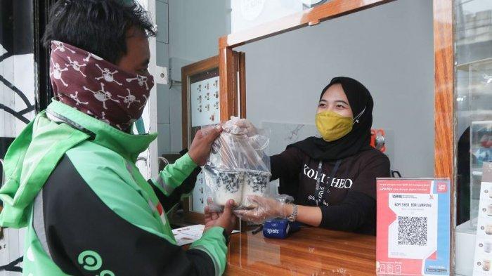 MERCHANT GOFOOD TERAPKAN J3K - Karyawan Kopi Sheo selaku merchant GoFood menyerahkan minuman pesanan konsumen kepada mitra driver GoFood di Kopi Sheo, Jalan Pagar Alam, Kedaton, Kota Bandar Lampung, Selasa (15/12/2020). Tampak karyawan Kopi Sheo menggunakan sarung tangan dan masker saat menyerahkan pesanan konsumen sebagai upaya menerapkan J3K (Jaga Kesehatan, Kebersihan, dan Keamanan).