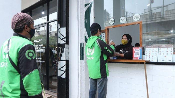 JAGA JARAK - Dua mitra driver antre dengan menjaga jarak untuk mengambil pesanan konsumen di Kopi Sheo, Jalan Pagar Alam, Kedaton, Kota Bandar Lampung, Selasa (15/12/2020). Penerapan jaga jarak oleh Kopi Sheo selaku merchant GoFood ini sebagai upaya menerapkan J3K (Jaga Kesehatan, Kebersihan, dan Keamanan).