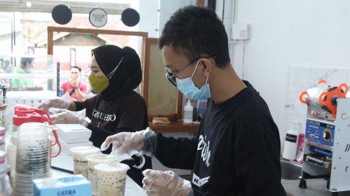 DISIPLIN J3K - Dua karyawan Kopi Sheo selaku merchant GoFood menyiapkan minuman pesanan konsumen di Kopi Sheo, Jalan Pagar Alam, Kedaton, Kota Bandar Lampung, Selasa (15/12/2020). Tampak karyawan Kopi Sheo menggunakan sarung tangan dan masker saat menyiapkan pesanan konsumen sebagai upaya menerapkan J3K (Jaga Kesehatan, Kebersihan, dan Keamanan).