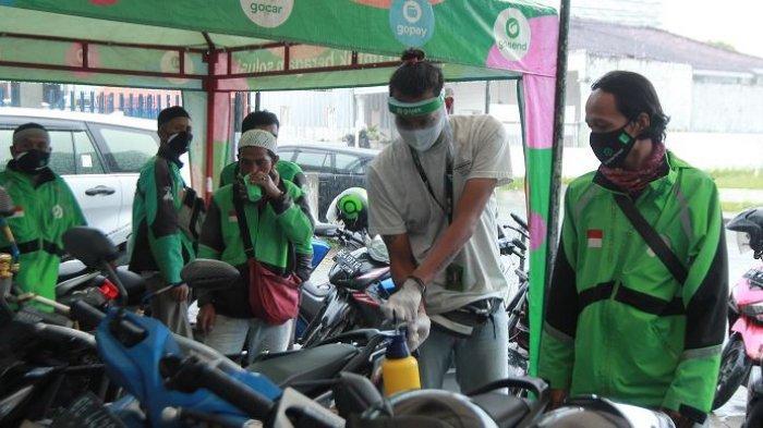 SEMPROT DISINFEKTAN - Petugas menyemprotkan disinfektan ke sepeda motor mitra driver Gojek di Posko Aman J3K, Kantor Gojek, Jalan Wolter Monginsidi, Kecamatan Telukbetung Utara, Kota Bandar Lampung, Senin (16/11/2020). Gojek mendirikan Posko Aman J3K di Lampung untuk melindungi mitra-mitranya dari penularan Covid-19 melalui pemeriksaan suhu tubuh, pemberian perlengkapan penunjang kesehatan, dan melakukan penyemprotan disinfektan pada kendaraan agar para konsumen tetap nyaman saat menggunakan transportasi ini di tengah pandemi Covid-19.