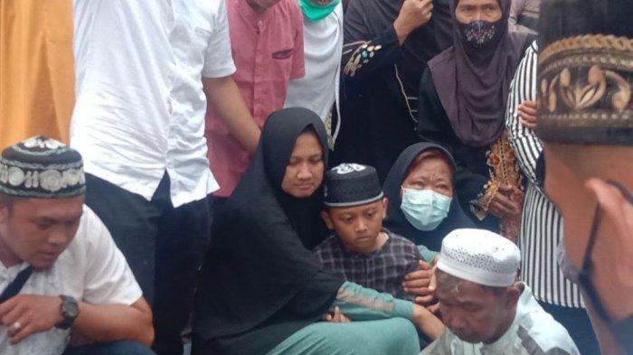 Istri Bripka Heri Bersama Putranya Duduk di Samping Makam Sambil Menangis