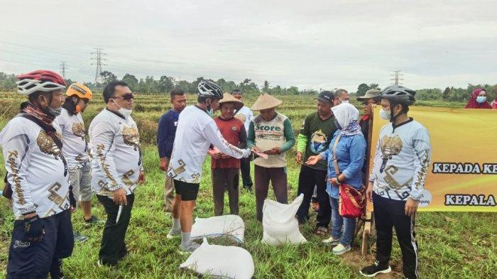 Sambil Bersepeda, Kajati Lampung Heffinur Bagikan Pupuk ke Petani di Metro Selatan