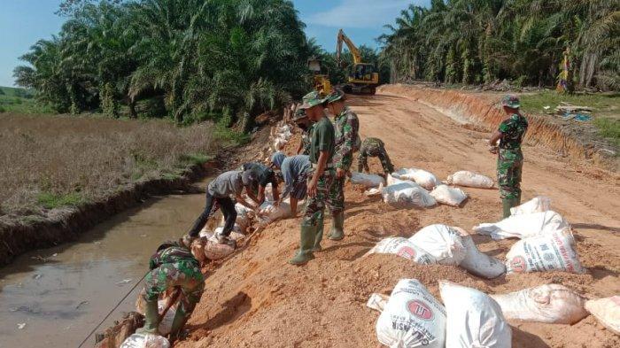 Anggota TNI Tulangbawang Lampung Pasang 800 Kayu Gelam Untuk Penahan Badan Jalan