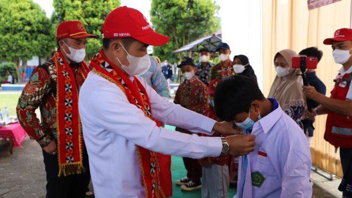 Bupati Lampung Barat Parosil Mabsus memakaikan seragam sekolah gratis kepada murid SMP Negeri 1 Kebun Tebu, Lampung Barat, Kamis (7/10/2021).