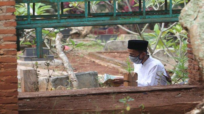 Penziarah berdoa di makam keluarga nya saat ziarah kubur di Tempat Pemakaman Umum (TPU) Kelenong, Sukajawa, Tanjungkarang Barat, Kamis (13/5/2021).