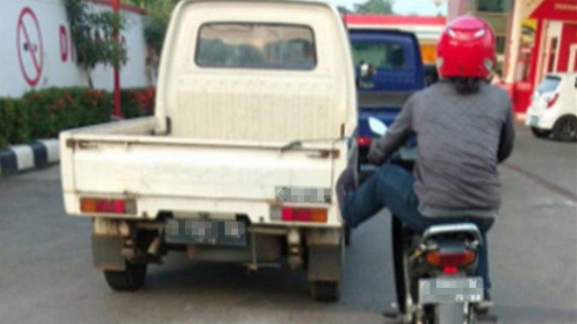 pemotor-mendorong-mobil-menggunakan-satu-kaki.jpg