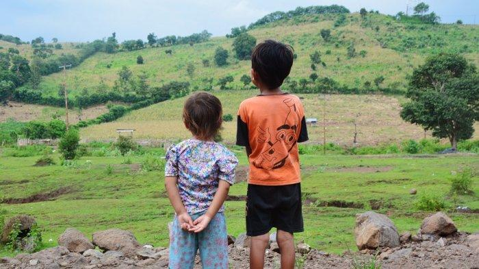 HUTAN GUNDUL: Anak-anak di Kabupaten Dompu, Provinsi NTB melihat ke arah hutan gundul yang beralih fungsi menjadi lahan tanaman jagung. Foto ini diambil 10 April 2019.