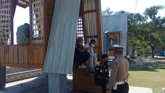 PATROLI: Anggota Polres Sumbawa membagikan masker kepada pengunjung di objek wisata, Minggu (6/6/2021). (Dok. Polres Sumbawa)