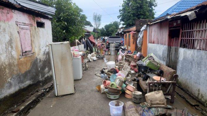 BERSIHKAN LUMPUR: Barang-barang rumah tangga ditumpuk warga di depan rumah untuk dibersihkan dari lumpur, usai banjir, Sabtu (3/4/2021).
