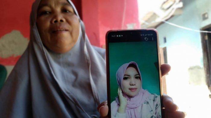 KORBAN: Hj Faridah, ibu korban menunjukkan foto Halimatulsadiah, wanita yang tewas ditusuk sang suami, Senin (19/4/2021).