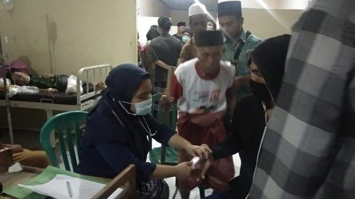 KERACUNAN: Warga yang mengalami keracunan berdatangan ke Puskesmas Janapria, Jumat (29/5/2021).(Dok. Polsek Janapria)