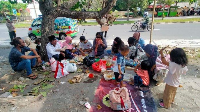 MAKAN KETUPAT: Usai melakukan ziarah makam dan 'ngurisan' di Makam Loang Baloq, rombongan asal Lombok Timur ini menyantap hidangan ketupat bersama di parkiran luar pemakaman, Kamis (20/5/2021).