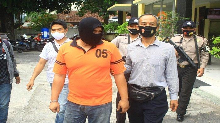 PENIPU: Pelaku pelenggapan 16 mobil sewa, RA (pakai baju tahanan) digiring anggota Polsek Ampenan, saat keterangan pers, Jumat (27/11/2020).