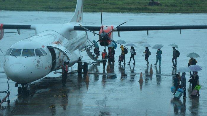 PENERBANGAN DOMESTIK: Para penumpang pesawat di Bandara Internasional Lombok berjalan menggunakan payung saat naik ke pesawat, Jumat (8/1/2021)