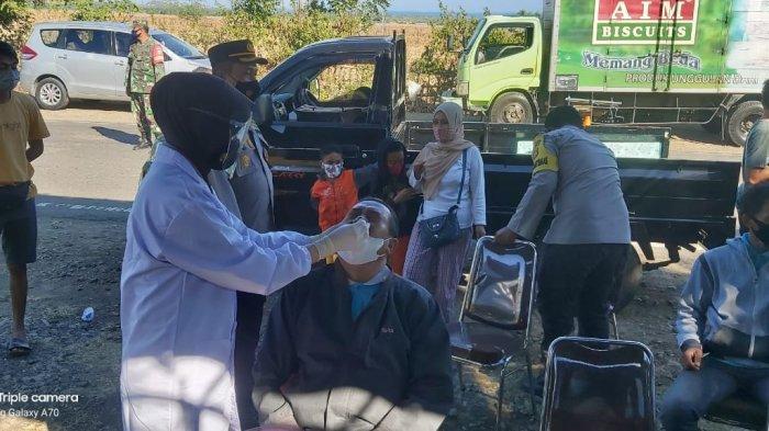 TES ACAK: Petugas kesehatan melakukan tes swab antigen kepada pengendara yang melintas di simpang H Hasyim, pintu masuk Sumbawa Barat, Sabtu (22/5/2021).(Dok. Polres Sumbawa Barat)