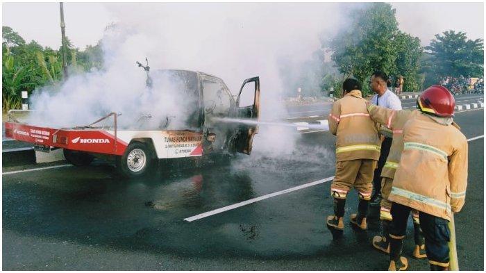 TERBAKAR: Petugas Pemadam Kebakaran Lombok Barat berusaha memadamkanapimobil pikap dealer yang terbakar, Sabtu (26/12/2020).