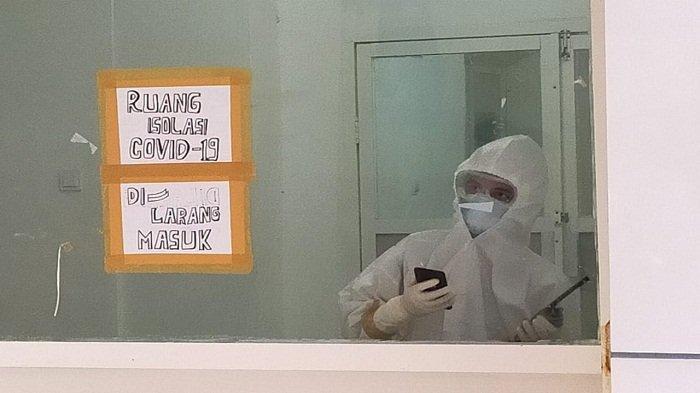 TENAGA KESEHATAN: Seorang tenaga kesehatan di ruang isolasi Covid-19 RSUD Kota Mataram melihat dari balik jendela.