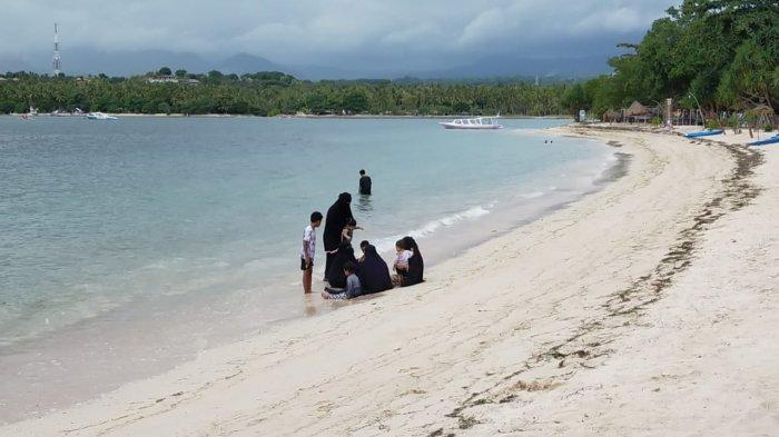 WISATA: Beberapa orang wisatawan lokal menikmati indahnya Pantai Sira di Lombok Utara, Minggu (27/6/2021).(TribunLombok.com/Sirtupillaili)