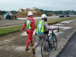 dua-orang-pekerja-berjalan-di-antara-proyek-pembangunan-sirkuit-motogp-mandalika.jpg