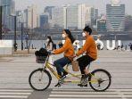 pasangan-yang-mengenakan-masker-naik-sepeda-tandem-di-sekitar-taman-di-seoul-pada-hari-sabtu.jpg