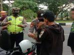petugas-kepolisian-menggeledah-barang-barang-milik-dua-pemuda-dalam-penyekatan-malam-tahun-baru.jpg
