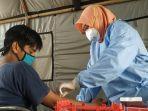 seorang-petugas-dinas-kesehatan-provinsi-ntb-mengambil-sampel-darah.jpg