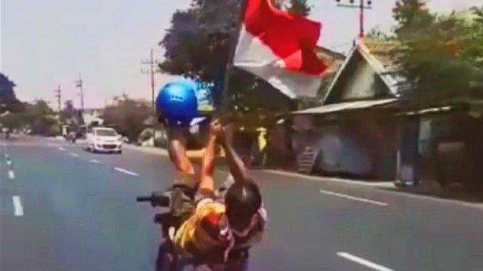 VIRAL, Aksi Berbahaya Pengendara Tiduran di Atas Motor sambil Kibarkan Bendera, Polisi Buru Pelaku