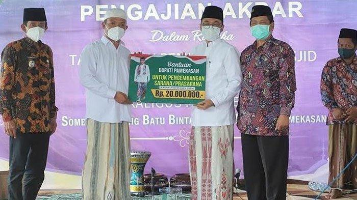Bupati Pamekasan, Baddrut Tamam (kanan) saat menyerahkan bantuan secara simbolis ke perwakilan pengurus Masjid Darul Karomah, Dusun Sumber Lumpang, Desa Batubintang, Kecamatan Batumarmar, Kabupaten Pamekasan, Jumat (5/3/2021).