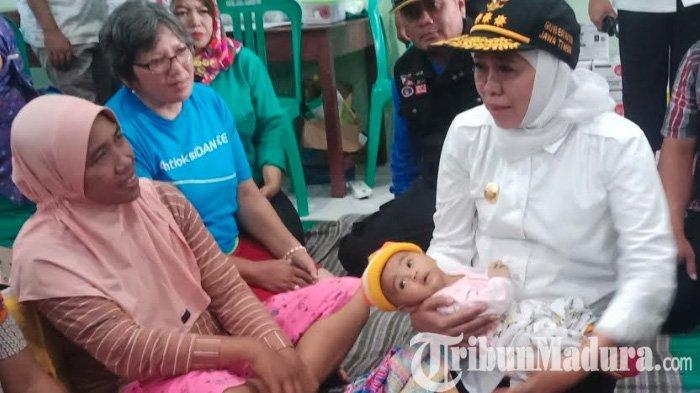 Tinjau Banjir Madiun, Gubernur Khofifah Gendong Bayi Nafisa yang Kekurangan Popok dan Makanan