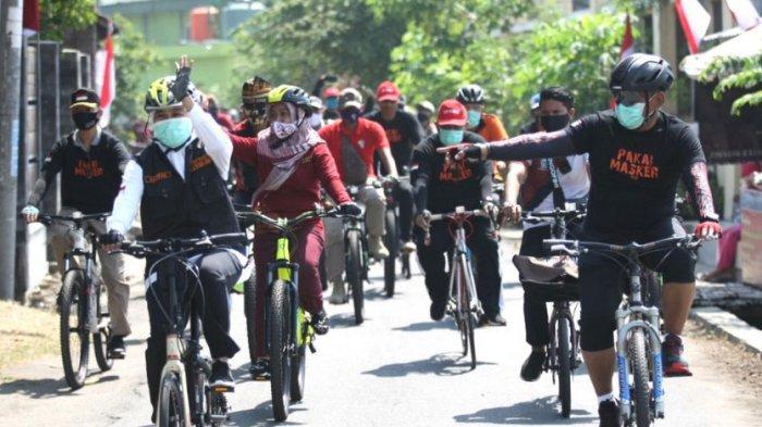 Bersama Penyintas Covid-19, Gubernur Khofifah Bersepeda Sembari Bagikan Masker di Kota Mojokerto