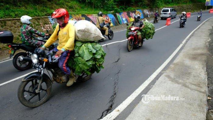 Para pengguna jalan lalu lalang melintasi jalan yang retak di kawasan Payung 1, Kota Batu, Kamis (15/2/2021).