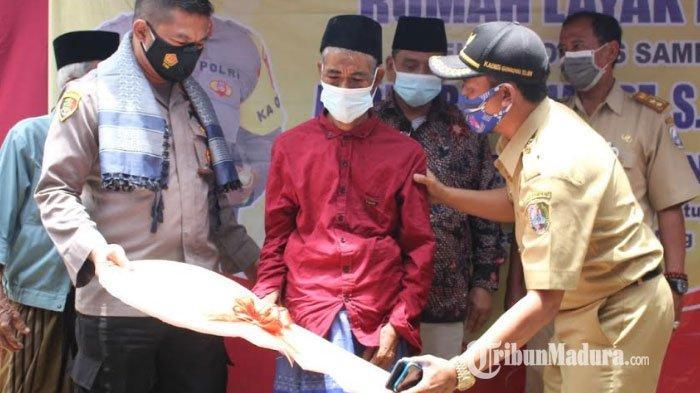 Kakek Fuadin bersama Kapolres Sampang AKBP Abdul Hafidz saat memotong pita penyerahan bantuan layak huni, Senin (22/2/2021).