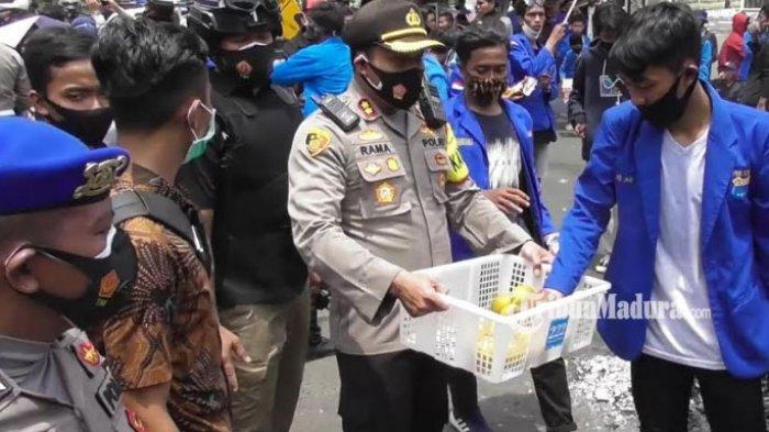 Kapolres Bangkalan AKBP Rama Samtama Putra membagikan buah jeruk ketika massa PMII Bangkalan menggelar aksi demo penolakan Omnibus Law UU Cipta Kerja di depan Gedung DPRD Bangkalan, Jalan Soekarno-Hatta, Jumat (9/10/2020).