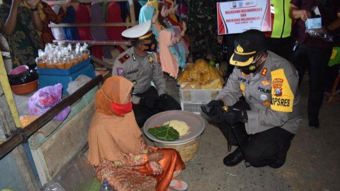 Kapolres Pamekasan, AKBP Apip Ginanjar saat memberikan masker gratis ke pedagang di Pasar 17 Agustus, Selasa (2/2/2021).