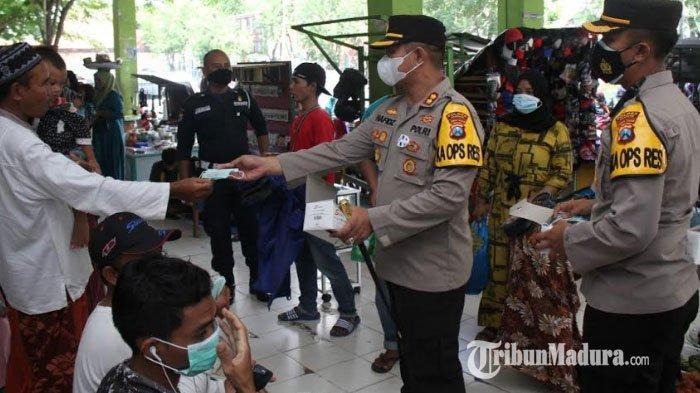 Kapolres Sampang, AKBP Abdul Hafidz saat membagikan masker kepada pengunjung dan pedagang di Pasar Srimangunan, Kabupaten Sampang, Madura, Selasa (2/2/2021).