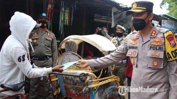 Kapolres Sumenep, AKBP Darman saat membagikan 500 masker bagi warga dan pedagang di Pasar Anom Baru Sumenep, Senin (1/2/2021).