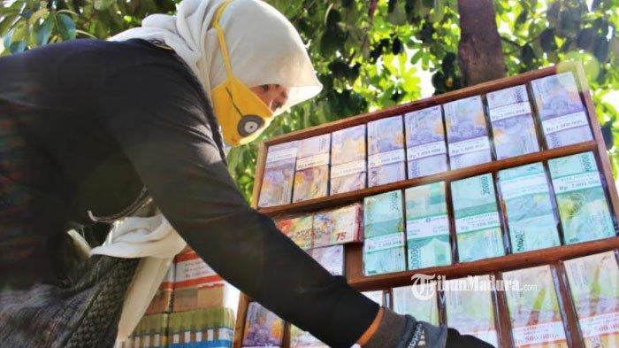 Yuli saat merapikan tatanan uang baru di lapak yang berada di pinggir Jalan Raya Mayjen Sungkono, Surabaya. Jumat (30/4/21).