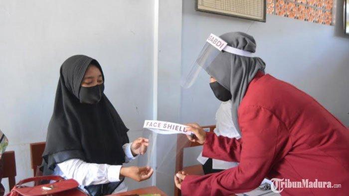Perangi Covid-19, MahasiswaUMM Bagikan Masker hinggaFace Shield untuk WargaDesa Gulbung Sampang