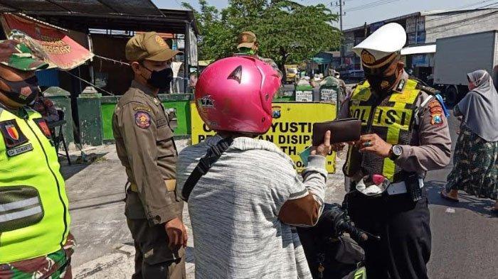 Operasi yustisi yang digelar petugas gabungan di Jalan Raya Saimbang, Kecamatan Sukodono, Kabupaten Sidoarjo. Sejumlah warga terkena tilang karena tidak memakai masker