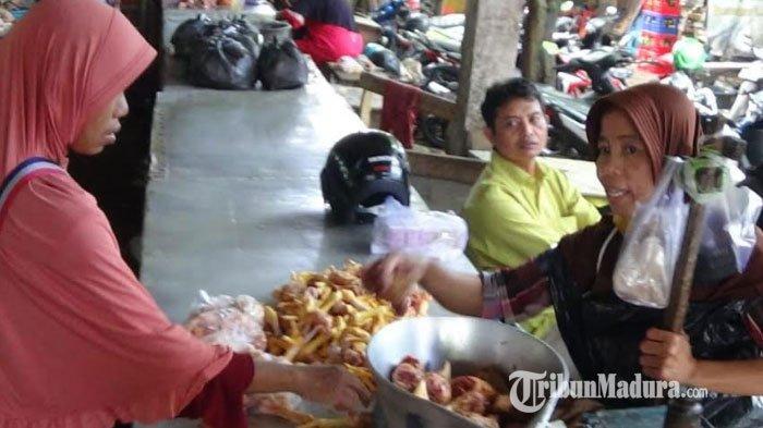 Pedagang daging ayam yang sedang melayani pembeli di Pasar Anom Baru, Kabupaten Sumenep, Madura, Jawa Timur, Senin (12/4/2021).