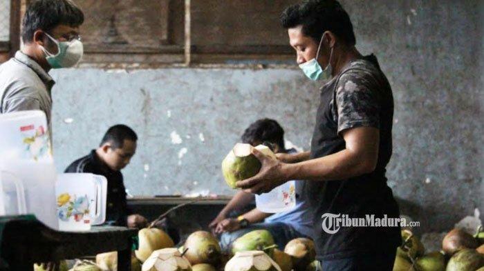 Pedagang penjual kelapa muda di kawasan Menur Surabaya saat melayani pembeli, Kamis (8/7/2021).