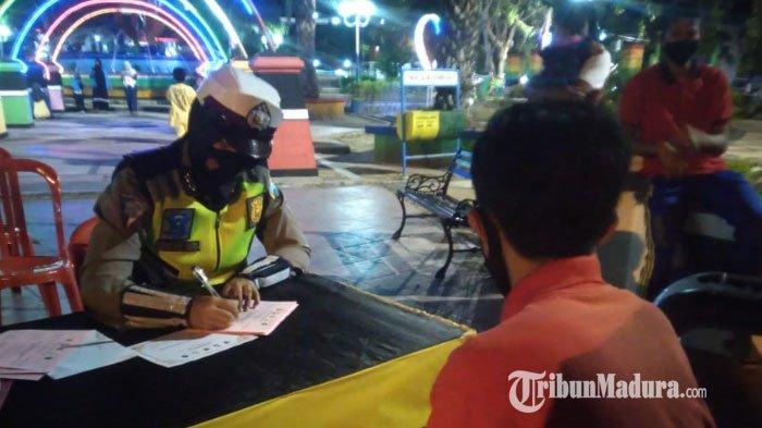 Pengunjung Taman Kota Sampang saat dikenakan sanksi tertulis lantaran tidak menggunakan masker, (15/9/2020) malam.