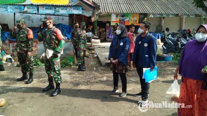 Personel Kodim Pamekasan saat berkolaborasi dengan mahasiswa KKN dari Unair Surabaya ketika membagikan masker gratis dan edukasi protokol kesehatan ke pedagang Pasar Gurem, Jumat (22/1/2021).