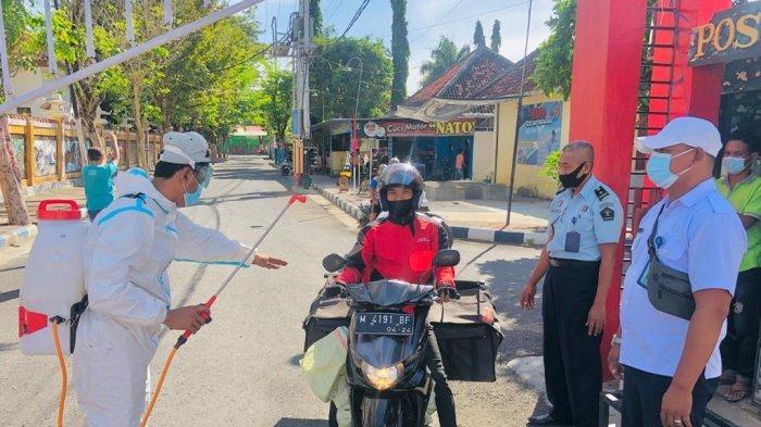 Petugas Lapas Kelas IIA Pamekasan saat melakukan penyemprotan disinfektan terhadap pengendara yang hendak masuk ke lingkungan Lapas Pamekasan, Madura, Jumat (9/7/2021).