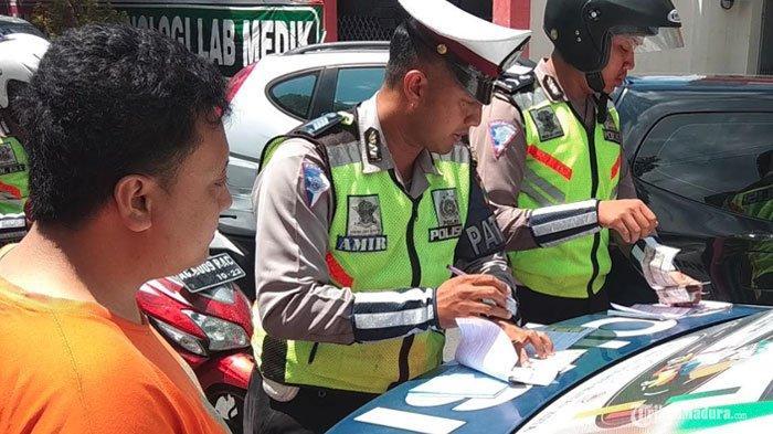 ILUSTRASI - Polisi menilang pengendara yang memarkir sepeda motornya di atas trotoar di Jalan Merdeka, Kota Blitar, Rabu (27/3/2019).
