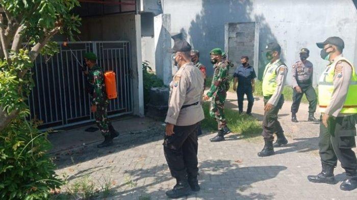 Suasana saat personel Polsek Pademawu menyemprotkan cairan disinfektan ke salah satu rumah warga Lawangan Daya, Kabupaten Pamekasan, Madura, Jumat (9/7/2021).