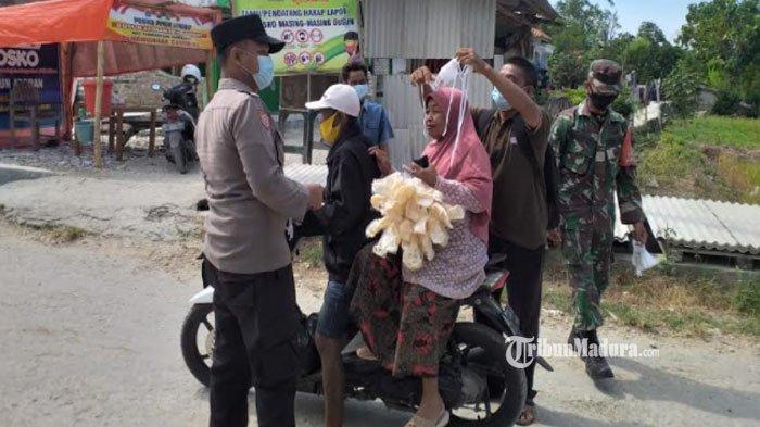 Gandeng Satgas PPKM Mikro Desa Ambat, Polsek Tlanakan Pamekasan Bagikan Masker Gratis ke Pengendara