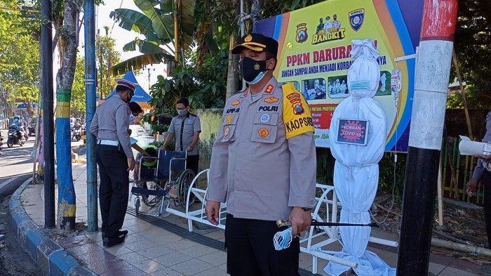 Suasana saat anggota Polres Pamekasan, Madura menggelar teatrikal pocong dan pasien Covid-19 di simpang empat Jalan Jokotole, Jumat (9/7/2021).
